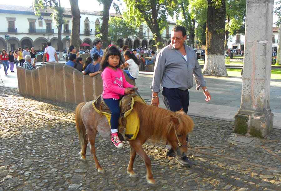 Little girl on pony and proud father, Patzcuaro, Mexico